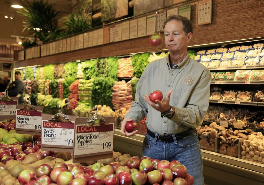 Whole Foods CEO John Mackey juggles apples as as he's photographed in one of his stores on New York's Upper West Side.  Photo: Richard Drew, AP