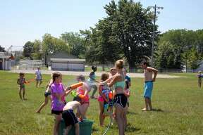 Kids in the Bad Axe Parks and Recreation program engage in a water fight in the scorching heat early Thursday afternoon.