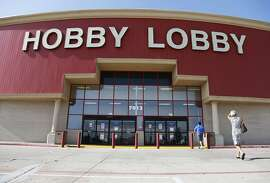 FILE - In this June 30, 2014, file photo, customers walk to a Hobby Lobby store in Oklahoma City. Federal prosecutors say Hobby Lobby Stores has agreed to pay a $3 million federal fine and forfeit thousands of ancient Iraqi artifacts smuggled from the Middle East that the government alleges were intentionally mislabled. Prosecutors filed a civil complaint in New York on Wednesday, July 5, 2017, in which Oklahoma City-based Hobby Lobby consented to the fine and forfeiture of thousands of tablets and bricks written in cuneiform, one of the earliest systems of writing, as well as other artifacts that prosecutors say were shipped without proper documentation. (AP Photo/Sue Ogrocki, File)