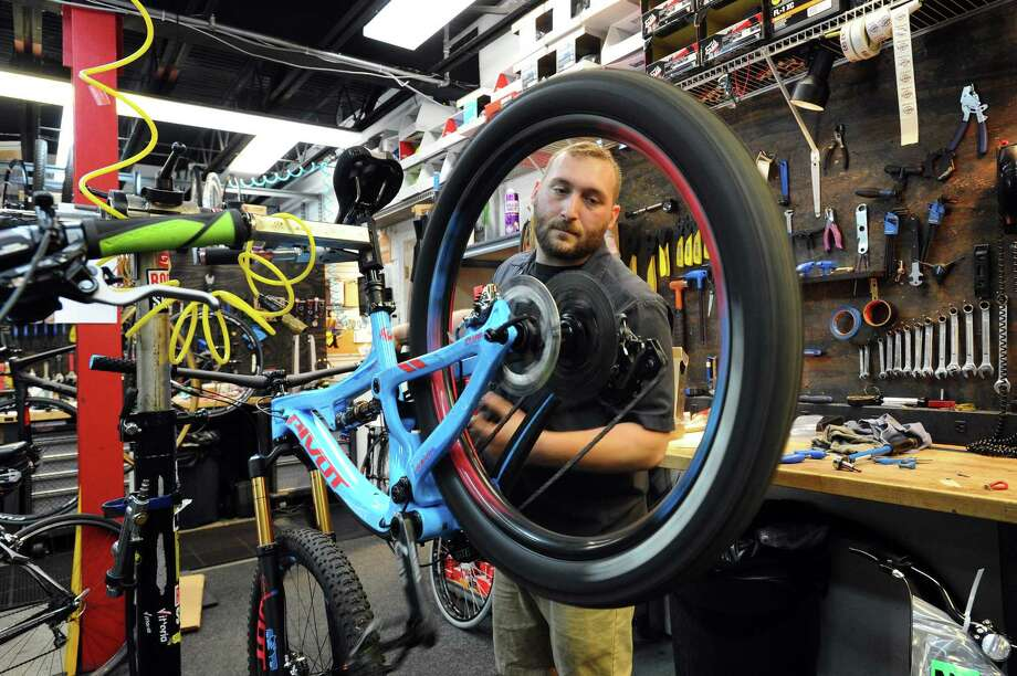 Danny's Cycles head mechanic Kevin Schmeiler spins the rear tire of a high-end off-road bicycle to make sure it is working properly, inside the bike shop at 1492 High Ridge Road in Stamford, Conn. on Thursday, June 29, 2017. Photo: Michael Cummo / Hearst Connecticut Media / Stamford Advocate