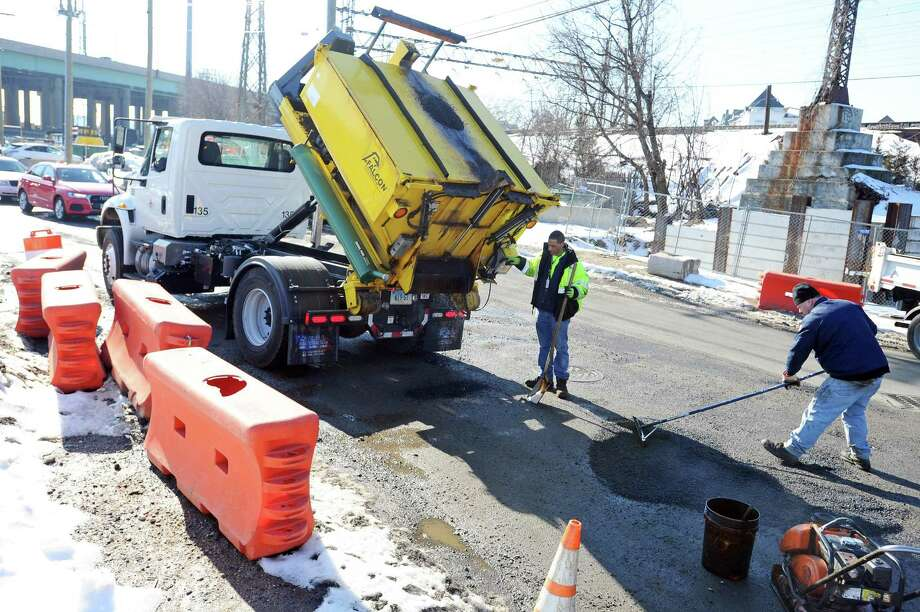 A city crew fills potholes on Myrtle Ave., on the corner of E. Main St., in Stamford, Conn. on Tuesday, Feb. 14, 2017. Photo: Michael Cummo / Hearst Connecticut Media / Stamford Advocate