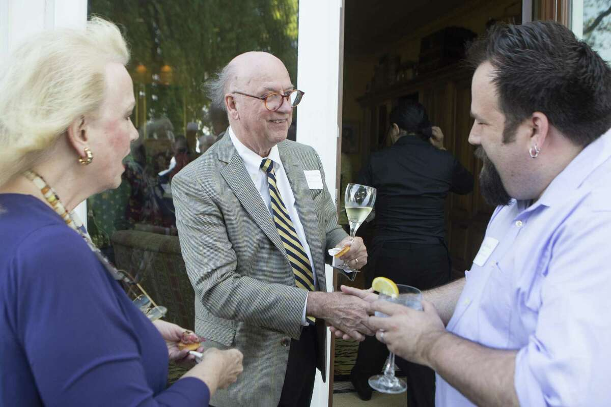 Jan Dilenschneider, left, looks on as with Samuel Quigley, center, shakes hands with Jeffrey Mueller. More than 25 gallery owners and museum officials during a Sunday Arts & Style round table at the Dilenschneider home in Dairen on Wednesday, May, 17, 2017