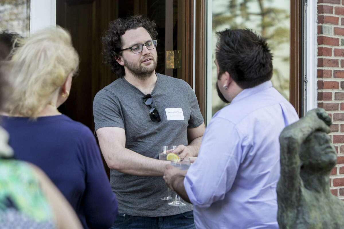Christopher Wyant, center, shakes the hand of Jeffrey Mueller right, while Jan Dilenschneider, left, looks on. More than 25 gallery owners and museum officials during a Sunday Arts & Style round table at the Dilenschneider home in Dairen on Wednesday, May, 17, 2017