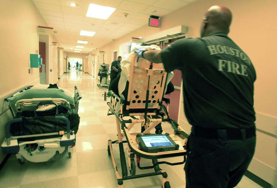 "Houston Fire fighters take a patient to another section of the emergency room at Memorial Hermann - Texas Medical Center in 2013. It is a common occurrence in Texas — an emergency room visit results in a ""surprise bill"" because the hospital brought in an out-of-network health provider. This should be illegal in Texas. Photo: Mayra Beltran /Houston Chronicle / © 2013 Houston Chronicle"
