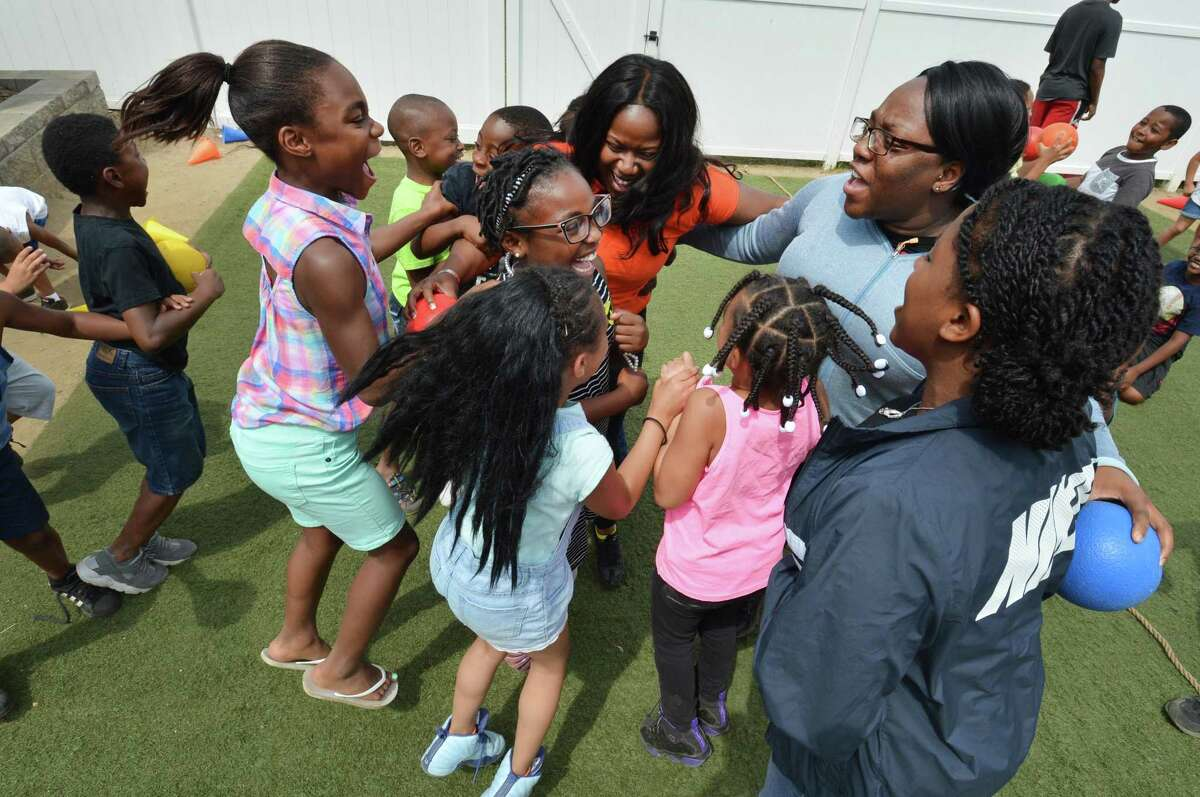 Educational Coorodinators Sasha James and Widline Brumaire celebrate with the kids after winning a game of cone dodge ball outside the Norwalk Housing Authority Learning Center at Colonial Village on Thursday June 29, 2017 in Norwalk Conn