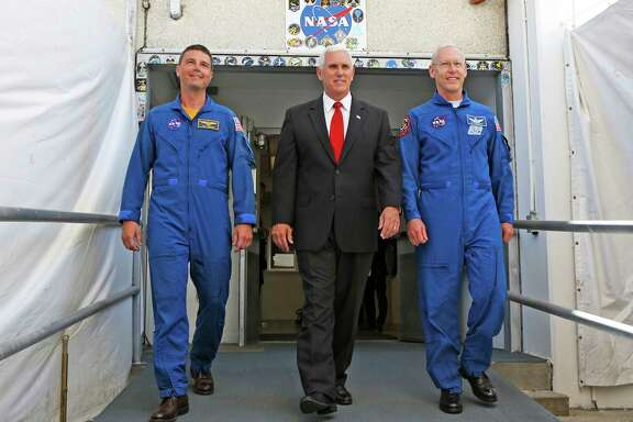 Vice President Mike Pence, center, is flanked by NASA astronaut Reid Wiseman, left, and Patrick Forrester, NASA Chief astronaut as they walk out of crew headquarters at the Kennedy Space Center in Cape Canaveral, Fla., on Thursday, July 6, 2017. Pence is leading a newly revived National Space Council. (Red Huber/Orlando Sentinel via AP)
