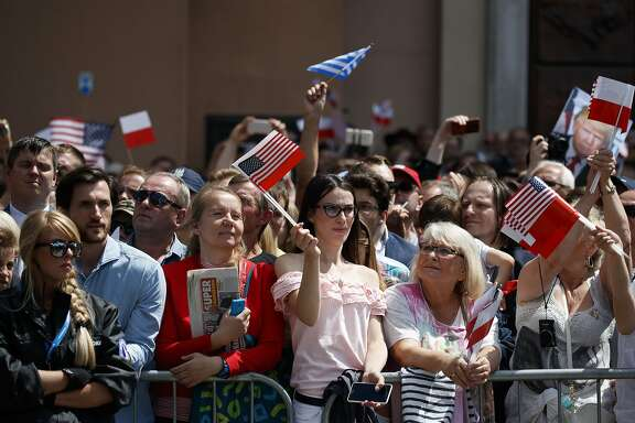 People wave flags as they listen as President Donald Trump speak at Krasinski Square at the Royal Castle, Thursday, July 6, 2017, in Warsaw. (AP Photo/Evan Vucci)