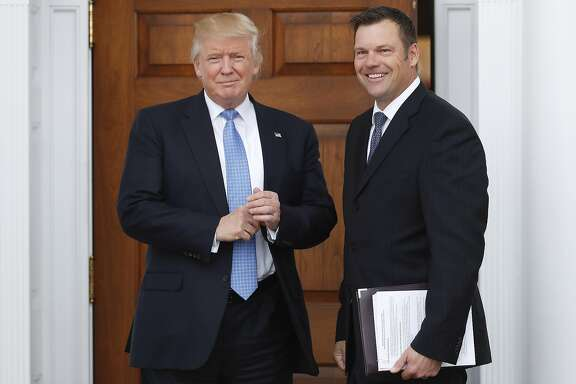 FILE - In this Nov. 20, 2016, file photo, Kansas Secretary of State Kris Kobach, right, holds a stack of papers as he meets with then President-elect Donald Trump at the Trump National Golf Club Bedminster clubhouse in Bedminster, N.J. Civil rights advocates say Kobach is trying to hide materials that undercut his public claim that substantial numbers of noncitizens have registered to vote. The American Civil Liberties Union obtained the documents as part of its federal civil lawsuit in Kansas challenging the state's proof-of-citizenship document requirement. It wants to court to remove the confidential designation Kobach placed on materials he was photographed taking into a November meeting. (AP Photo/Carolyn Kaster, File)
