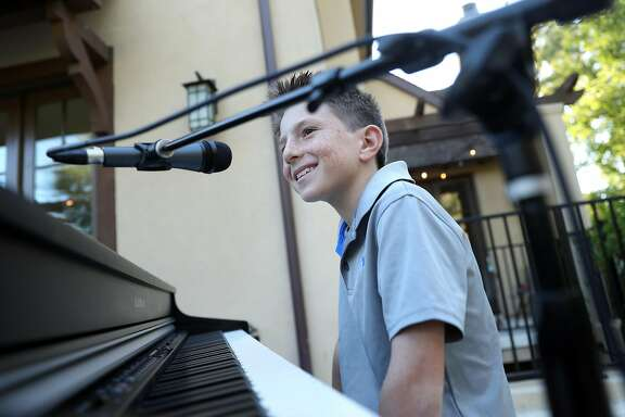 Lucca Mazzie, 9, smiles after performing with kid band Good Stuff in the backyard of his family's home in Menlo Park, Calif., on Thursday, June 29, 2017.