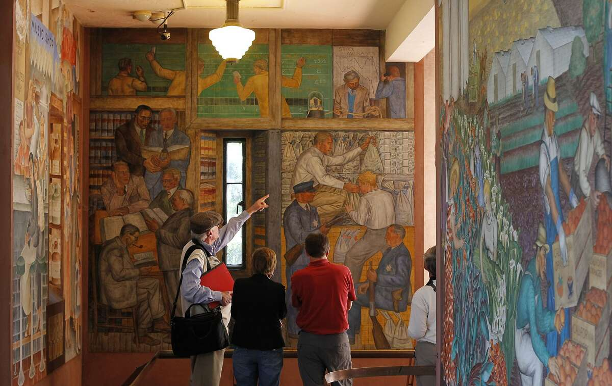 Visitors tour the many murals that fill the walls of eighty year old Coit Tower on Wednesday Oct. 16, 2013, in San Francisco, Calif. The San Francisco Parks and Recreation department is set to vote on a restoration project that would close down Coit Tower for five months to address several problems from flaking paint to a crumbling exterior.