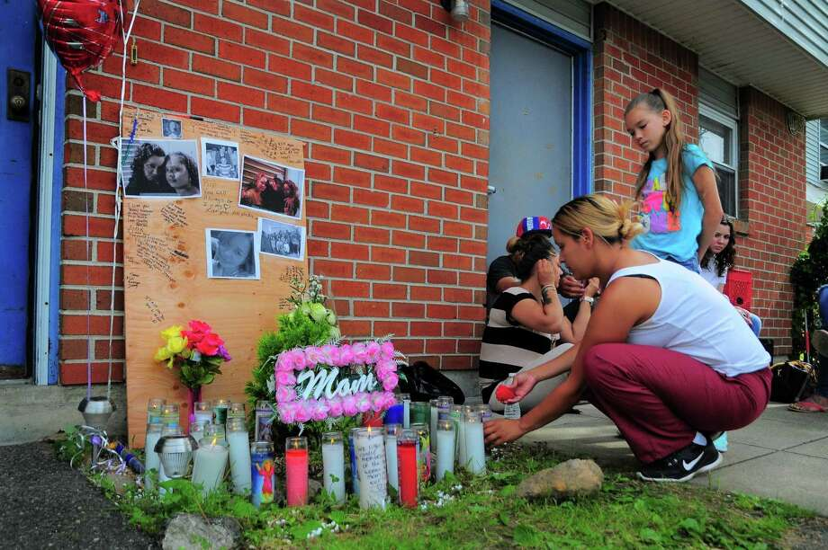 Family and friends of victim Jennifer Knox gather at a memorial set up outside the apartment where a murder suicide took place on Wednesday, in the Trumbull Gardens apartments in Bridgeport, Conn. on Thursday July 6, 2017. Photo: Christian Abraham / Hearst Connecticut Media / Connecticut Post