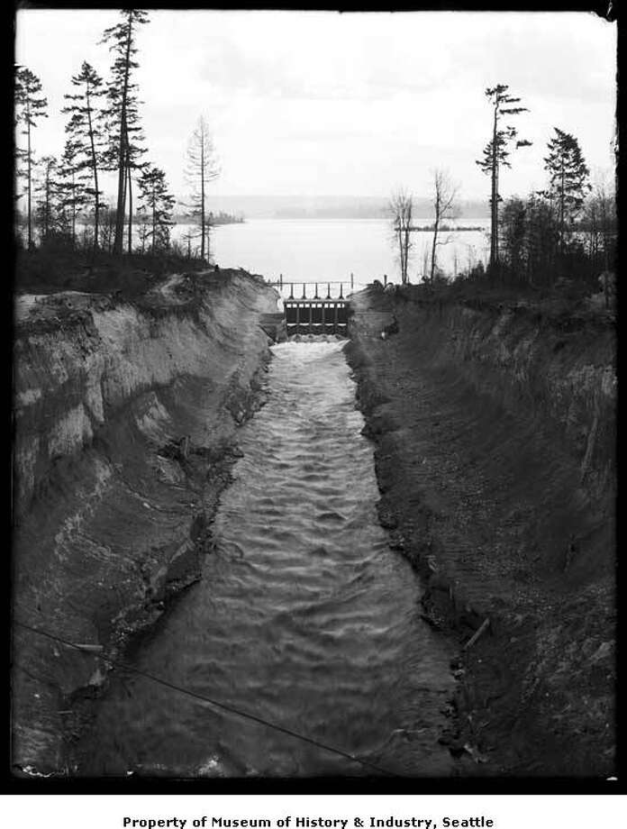 """""""Before the building of the Lake Washington Ship Canal, a small canal connected Lake Washington with Lake Union's Portage Bay. This photo, taken around 1911, shows the canal in the Montlake area and a dam which controlled the water level. Webster Point, at Laurelhurst, is in the distant left."""" -MOHAI. Photo courtesy MOHAI, PEMCO Webster and Stevens Collection, image number 1983.10.9159. Photo: Courtesy MOHAI"""