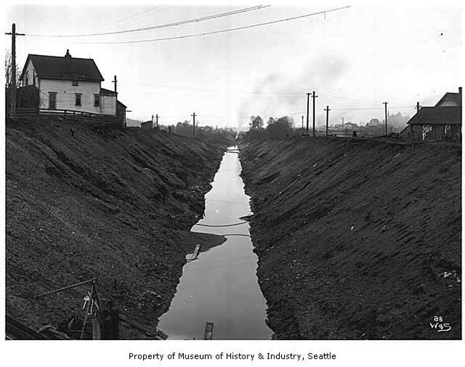 """Several small canals once connected Puget Sound, Lake Union and Lake Washington. These waterways were large enough to move logs but too small for boats. They were replaced by the Lake Washington Ship Canal, which opened in 1917. This photo shows a narrow portion of the canal in about 1904, before the Lake Washington Ship Canal was built. The photo may have been taken between Lake Union and Salmon Bay. Heavy earthmoving machinery may be seen in the far distance (center)."" MOHAI. Photo courtesy MOHAI, PEMCO Webster and Stevens Collection, image number 1983.10.6576.1. Photo: Courtesy MOHAI"