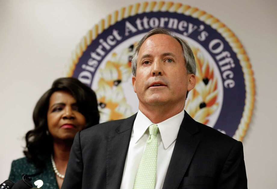 Texas Attorney General Ken Paxton, center, makes comments during a news conference as Dallas County District Attorney Faith Johnson, left, listens, Wednesday, June 22, 2017, in Dallas. (AP Photo/Tony Gutierrez) Photo: Tony Gutierrez, STF / Copyright 2017 The Associated Press. All rights reserved.
