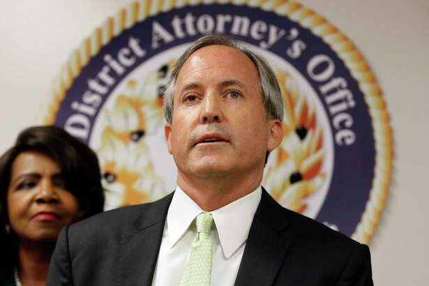 Texas Attorney General Ken Paxton, center, makes comments during a news conference as Dallas County District Attorney Faith Johnson, left, listens, Wednesday, June 22, 2017, in Dallas. (AP Photo/Tony Gutierrez)