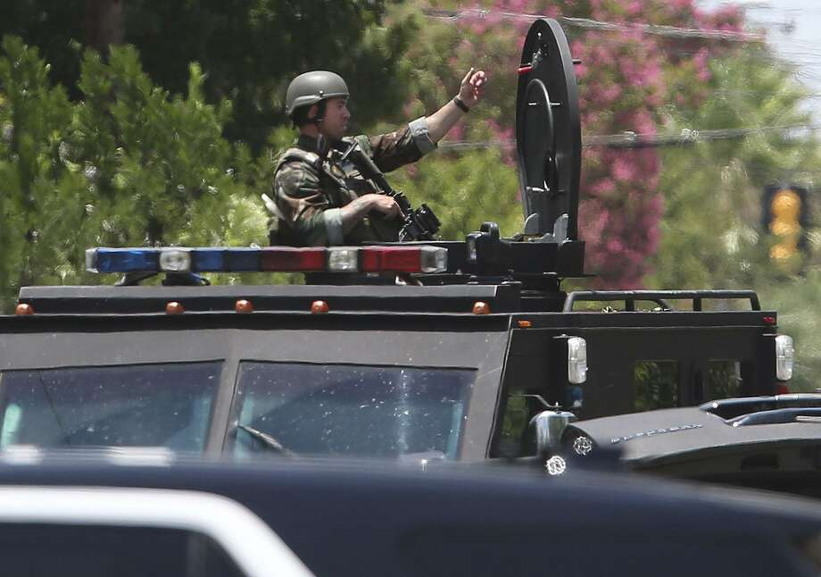 A SWAT officer monitors a situation Thursday at a home in the 500 block of Evergreen just north of downtown San Antonio. Photo: John Davenport /San Antonio Express-News / ©John Davenport/San Antonio Express-News