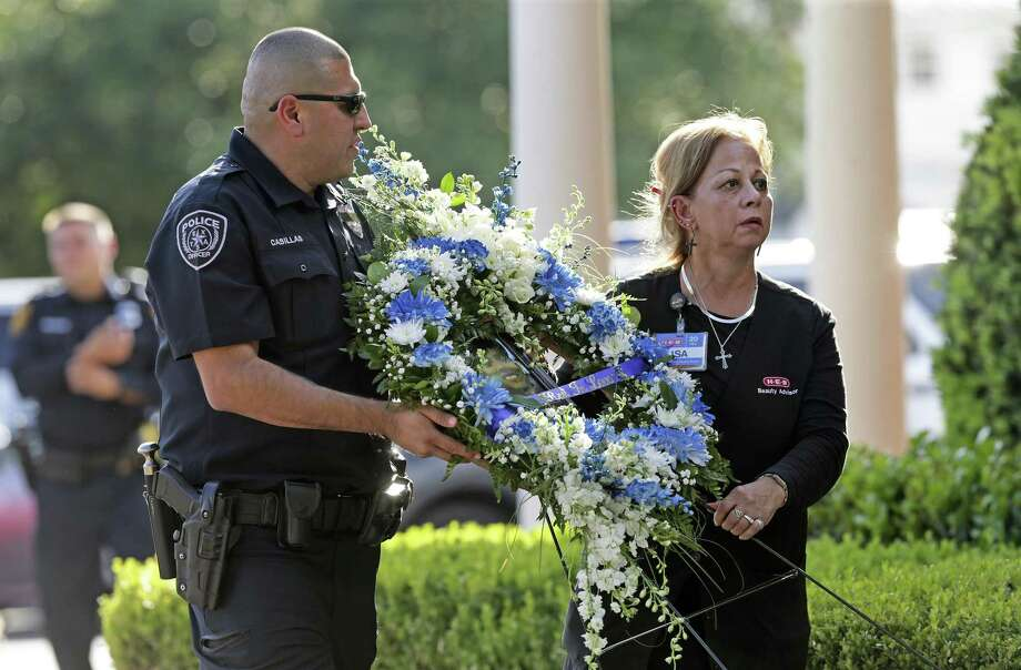A wreath is delivered by police officers as mourners exit the Porter Loring Funeral home after a viewing of Ofc. Miguel Moreno on July 6, 2017. Photo: Tom Reel, Staff / San Antonio Express-News / 2017 SAN ANTONIO EXPRESS-NEWS