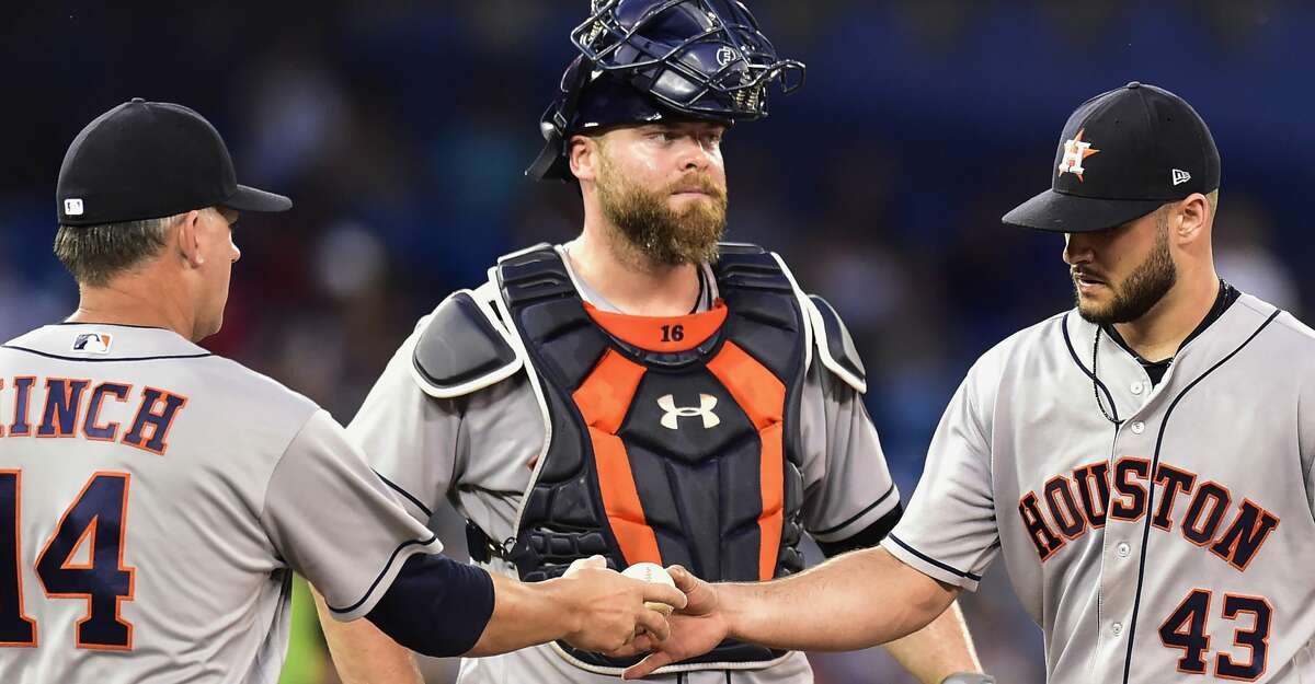 Houston Astros manager A.J. Hinch (14) takes the ball from starting pitcher Lance McCullers Jr. as he pulls McCullers from the baseball game as catcher Brian McCann watches in Toronto on Thursday, July 6, 2017. (Frank Gunn/The Canadian Press via AP)