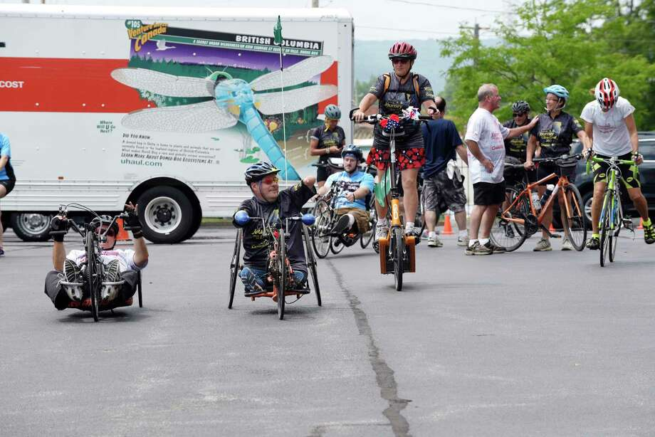 Doug Hamlin, left, VP of Operations for Our Ability, and John Robinson, second from left, CEO of Our Ability, head out with other cyclists after an event at the Golub Corporation Headquarters on Thursday, July 6, 2017, in Schenectady, N.Y.  Our Ability riders are taking part in a 12-day/364 mile bike ride fro Buffalo to Albany along the Erie Canal.  The ride is held each year to raise awareness and money to build employment and empowerment opportunities for people with disabilities.   (Paul Buckowski / Times Union) Photo: PAUL BUCKOWSKI / 20040986A
