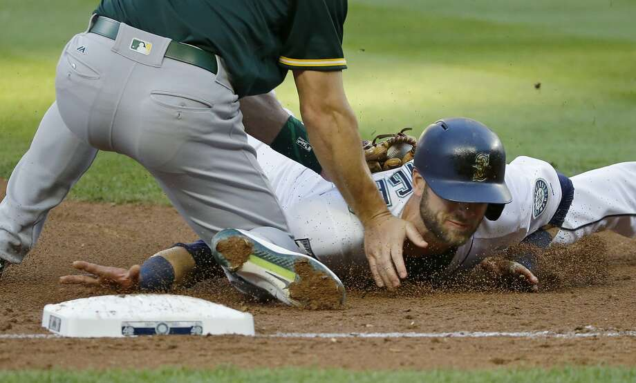 Seattle Mariners' Mitch Haniger, right, is tagged out at third base by Oakland Athletics third baseman Matt Chapman during the third inning of a baseball game, Thursday, July 6, 2017, in Seattle. Haniger was trying to advance after a fly ball hit by Jarrod Dyson was caught by Oakland Athletics center fielder Jaycob Brugman. (AP Photo/Ted S. Warren) Photo: Ted S. Warren, Associated Press