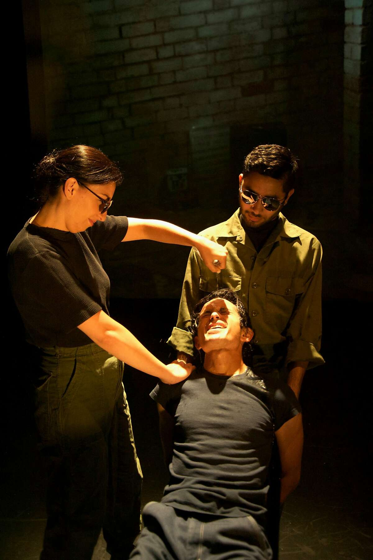 Top, from left:�Livia Gomes and�Ryan Vasquez as soldiers torturing Tim Garcia as Javier Alfaro, seated,�in