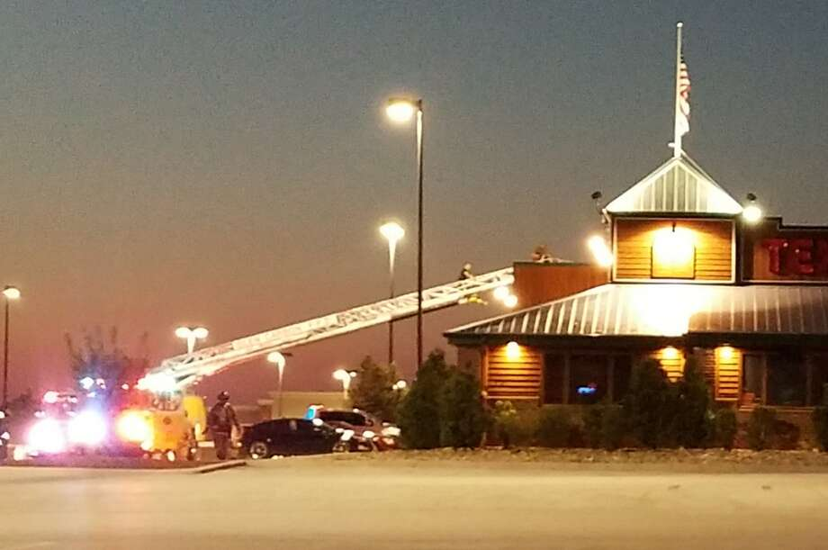 Glen Carbon Fire Protection District firefighters climb to the roof of Texas Roadhouse Thursday evening to check for possible problems. Photo: Carol Arnett • Carnett.edwi@gmail.com