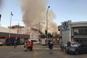 People evacuated from their home homes watch from the streeet as a building under construction burns early Friday near the intersection of Valdez and 23rd streets in Oakland.