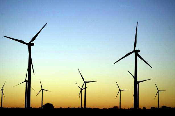 Giant wind turbines dot the sky at dawn near Honrrubia, central Spain, in this February 11, 2004 file photo. Europeans celebrate European Wind Day on June 15, 2007 to raise awareness of the power, popularity and effectiveness of wind energy right across Europe. Spain is the world's second-largest producer of wind power after Germany. REUTERS/Sergio Perez/Files (SPAIN)