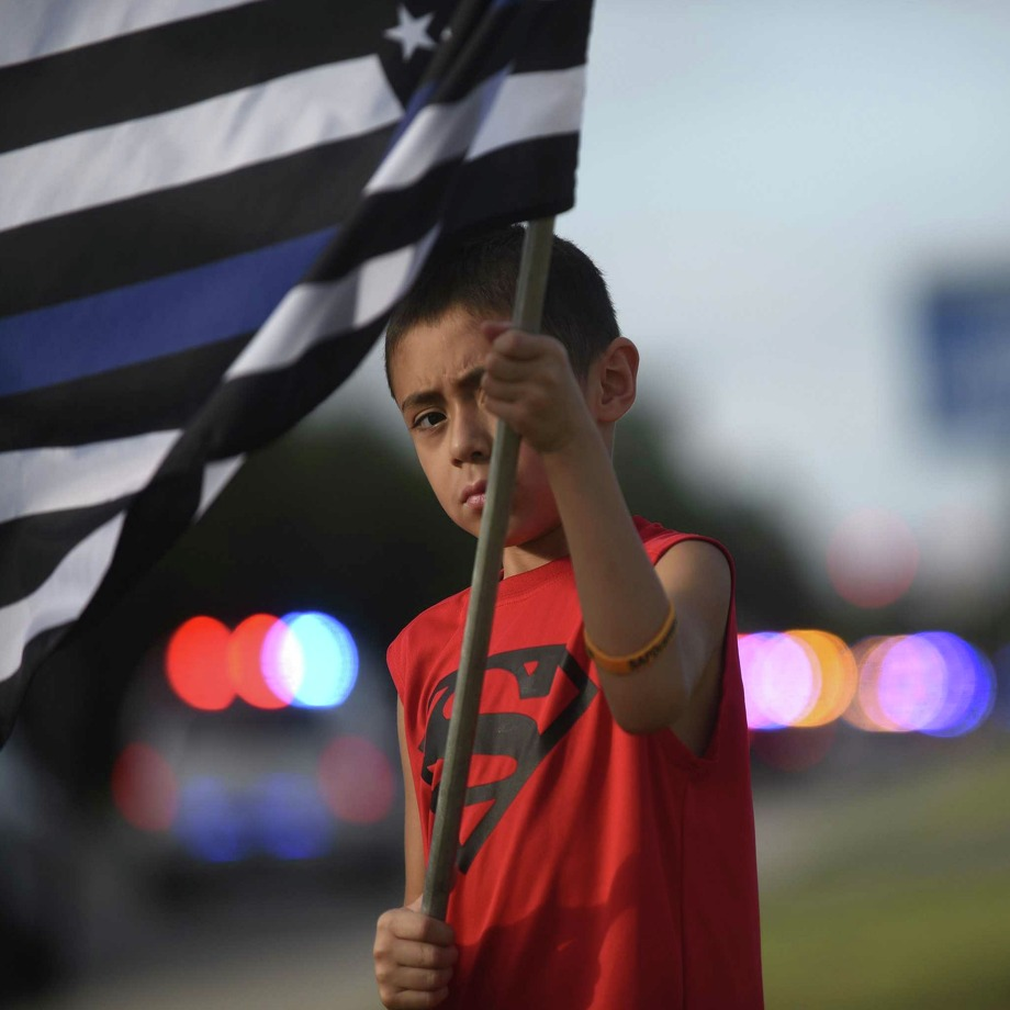 "Matthew Medrano, 7, waves a ""thin blue line"" flag as police  vehicles in the procession of slain San Antonio Police Officer Miguel Moreno leave the Alamodome staging area on Friday, July 7, 2017. Officer Moreno was gunned down in a shootout on June 29 and died the next day. Photo: Billy Calzada, Staff / San Antonio Express-News / San Antonio Express-News"