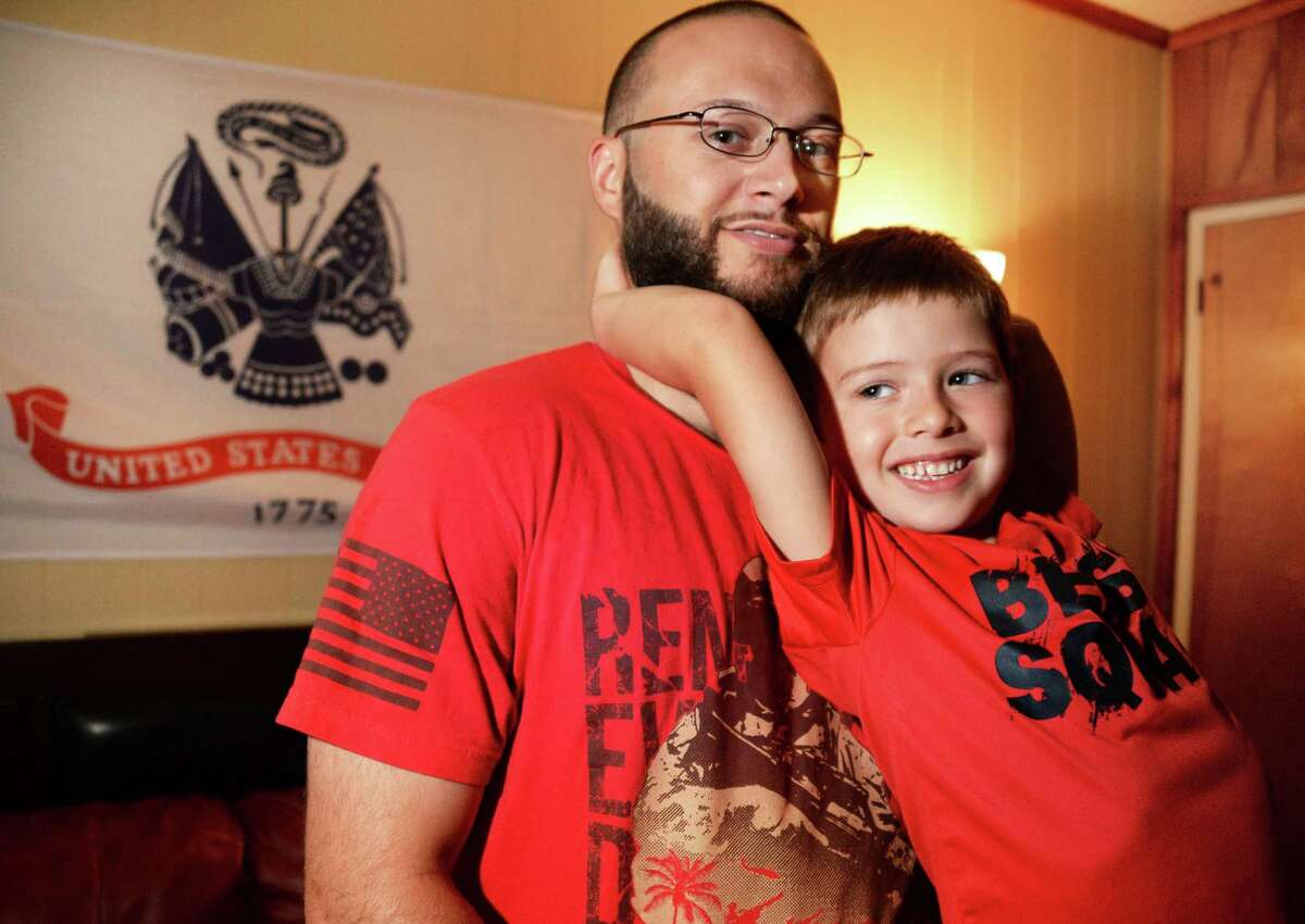 Iraq War veteran Dustin Greco, 27, who received a less than honorable discharge from the Army in 2010 and was later diagnosed by a VA therapist with a depressive disorder related to his military service, poses with his 5-year-old son, Christian, at his home in Cohoes, N.Y.