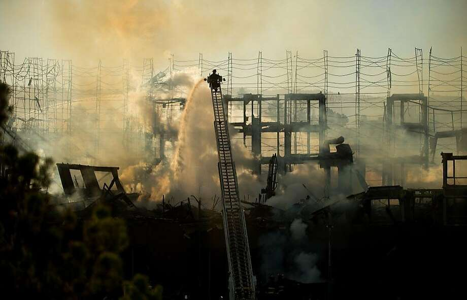 Firefighters battle a building fire at Valdez and 23rd streets in Oakland on July 7. Photo: Noah Berger, Special To The Chronicle