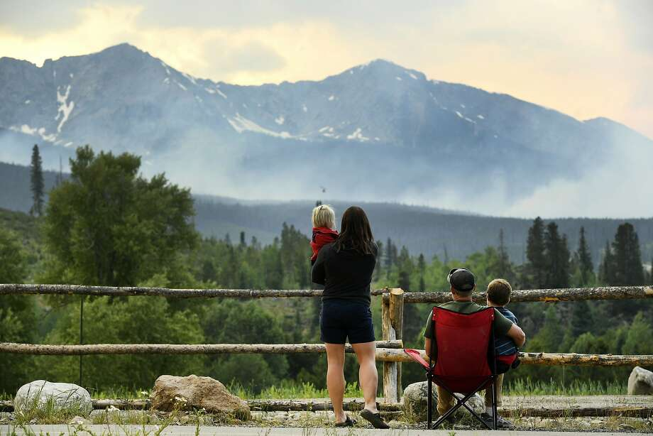 A family watches as helicopters dump water on a wildfire near the historic town of Breckenridge, Colo., on Thursday, the day after the fire was reported. Photo: Helen H. Richardson, Associated Press