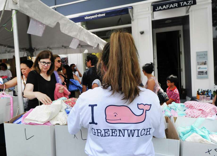 Vineyard Vines employee Morgan Blank, wears her company's trademark pink whale shirt, as she helps customers shopping outside the store during the annual Sidewalk Sales organized by the Greenwich Chamber of Commerce on Greenwich Avenue, Greenwich, Conn., Thursday, July 14, 2016. The 2017 event will be held Thursday, July 13, to Saturday, July 15, from 10 a.m. to 6 p.m. and Sunday, July 16, from 11 a.m. to 5 p.m. Photo: Bob Luckey Jr. / Hearst Connecticut Media / Greenwich Time