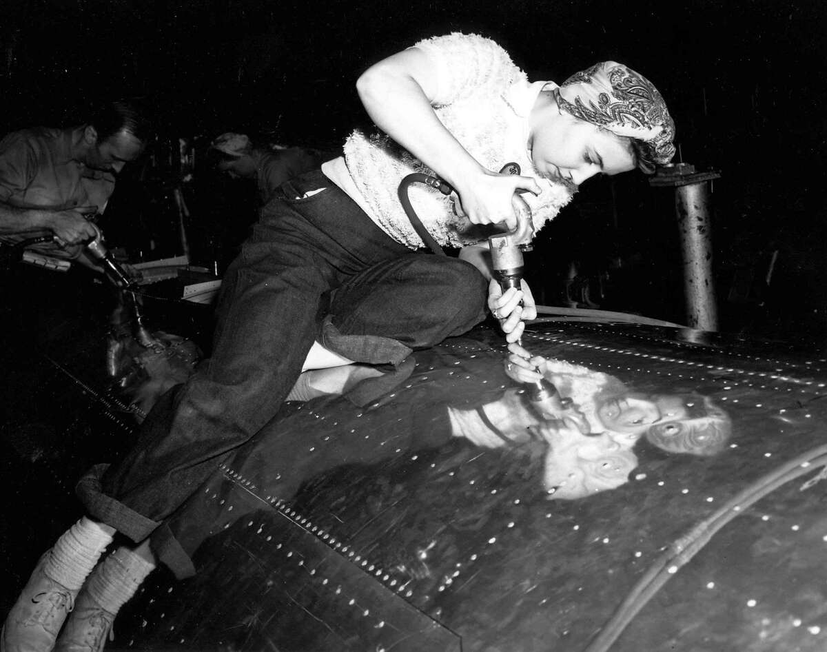 Mary Ann Johnson rivets the skin onto a Boeing bomber in this undated photo. IN 1942, about 15 percent of Boeing employees were women. By 1944 they rose to more than 40 percent. Rosie the Riveter