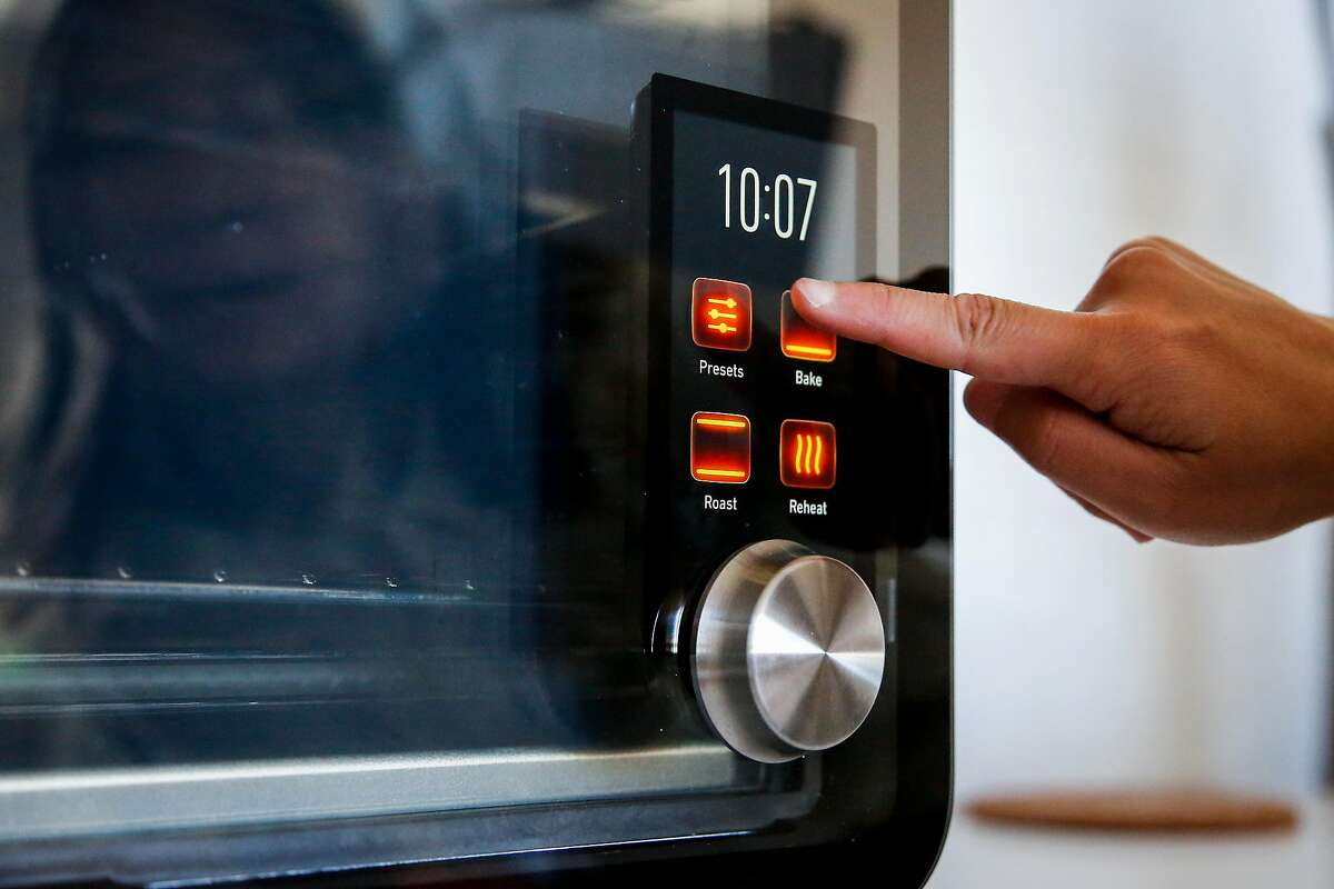 Emily Huh, marketing operation manager, demonstrates how to use the June Intelligent Oven, which detects what food is placed into it and how long it should be cooked, sits in the June studio in San Francisco on Thursday, July 6, 207.