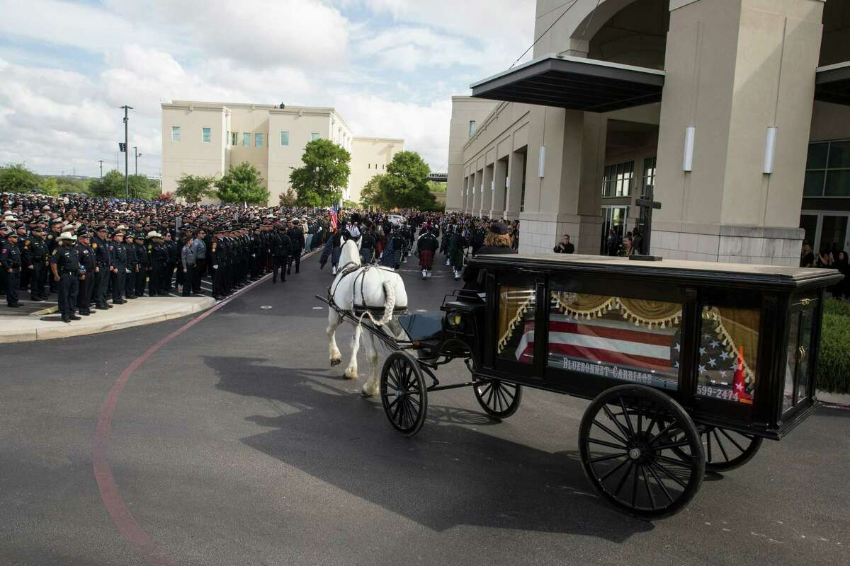 The casket carrying Officer Miguel Moreno III, who was killed in the line of duty, is brought in a horse-drawn carriage during the funeral procession at the Community Bible Church in San Antonio, Texas on July 7, 2017. His class and shift mates stood followed behind him.