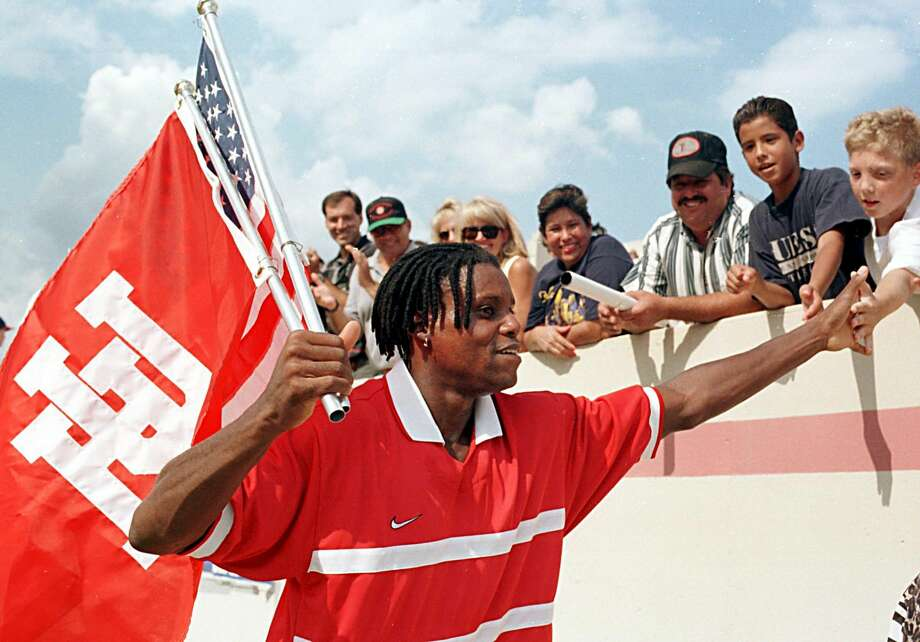 HOUSTON, TX - SEPTEMBER 13:  Olympian Carl Lewis high-fives fans on his victory lap following his farewell 400-meter relay race at Robertson Stadium on the campus of the University of Houston in Houston, TX, 13 September. Lewis, a University of Houston graduate, is carrying the University of Houston and American flags.  (Photo credit should read PAUL K. BUCK/AFP/Getty Images) Photo: PAUL K BUCK/AFP/Getty Images