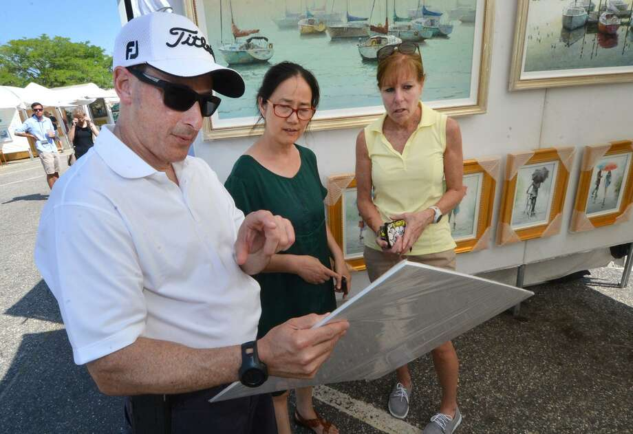 Mark and Sherrie Feder look at some nautical prints with Fang Liu, center, at the 2016 Westport Fine Arts Festival. The 2017 festival is Saturday and Sunday, July 15 and 16. Photo: Alex Von Kleydorff / Hearst Connecticut Media File Photo / Connecticut Post