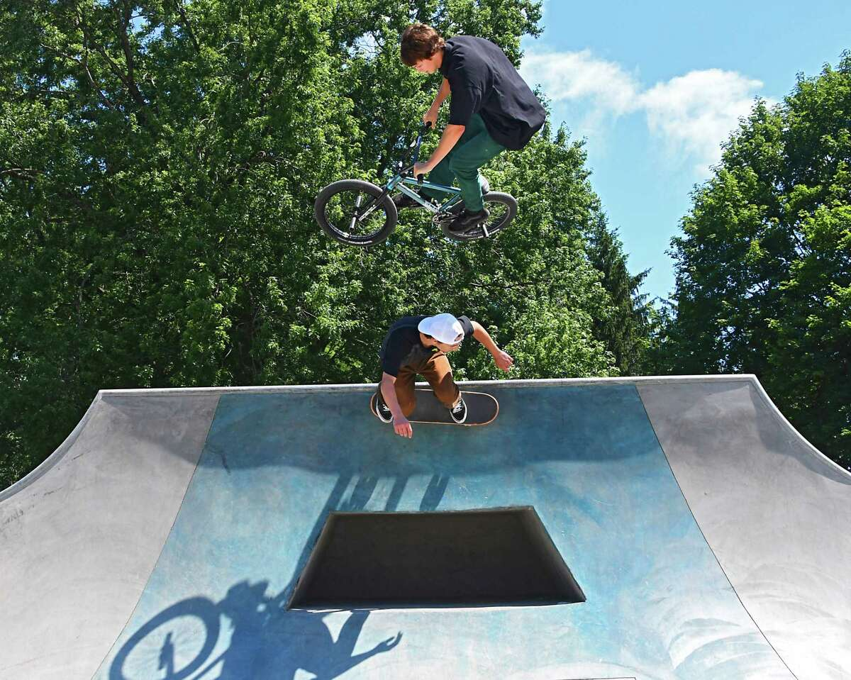 Mark Burnett of Albany rides his bike over his friend Dylan Longton of Slingerlands, who is riding his skateboard, after a ribbon-cutting to unveil the new Washington Park Skate Park on Friday, July 7, 2017 in Albany, N.Y. Dylan is on the skateboard committee who pushed for the park to be built. (Lori Van Buren / Times Union)