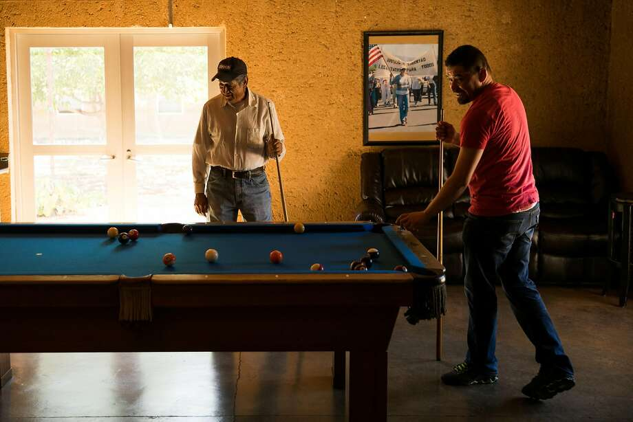 Vineyard workers Gorgonlo Gomez Figueroa (left) and Jose Valentin Ramirez play pool in the recreation room of the River Ranch farmworker housing center. Photo: Mason Trinca, Special To The Chronicle