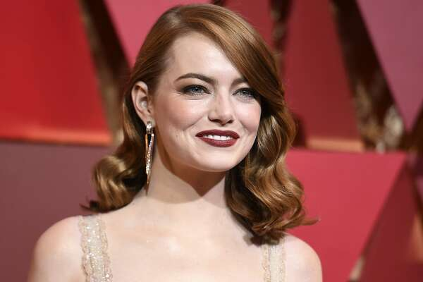 FILE - In this Feb. 26, 2017 file photo, actress Emma Stone arrives at the Oscars in Los Angeles. Stone says that male co-stars have taken pay cuts to ensure she received equal pay on films. Speaking to tennis great Billie Jean King in an interview published Thursday, July 6, in Out Magazine, Stone said the gesture to match has impacted what she's able to ask for in the future. (Photo by Richard Shotwell/Invision/AP, File)