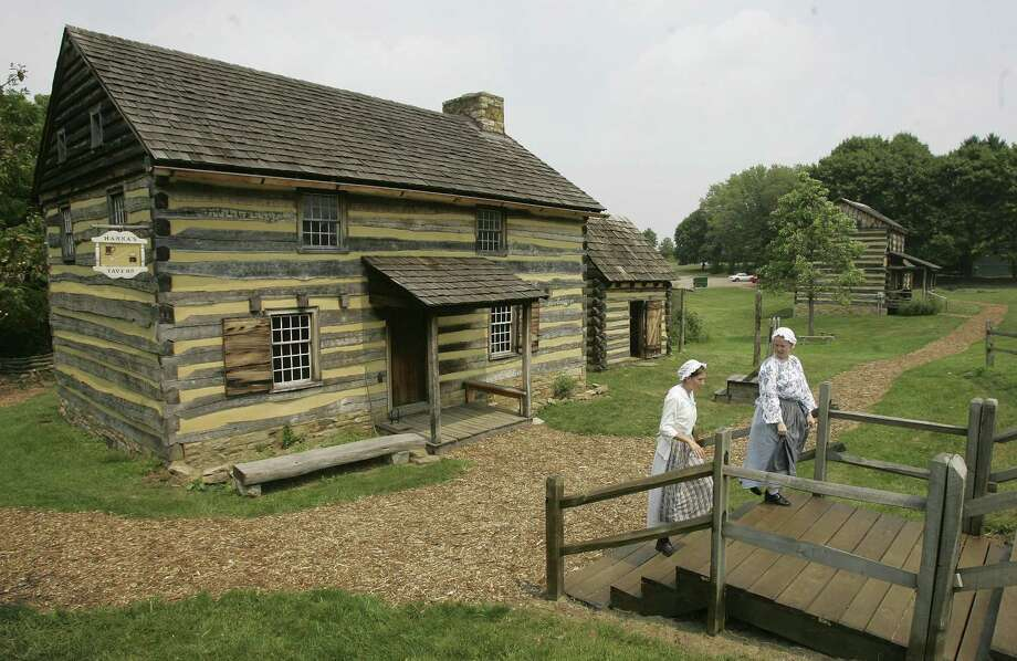 A theory: People vote for Trump against their best interest because he appeals to virtues and ideals of self sufficiency that were developed in frontier days and persist as cultural norms in modern days. Here, tour guides Zoe Johnson, left, and Kaitlin Davis walk from the cabin that recreates a tavern and courtroom from the era of the American Revolutionary War in Hanna's Town in Pennsylvania in 2007. Photo: Keith Srakocic /AP / AP