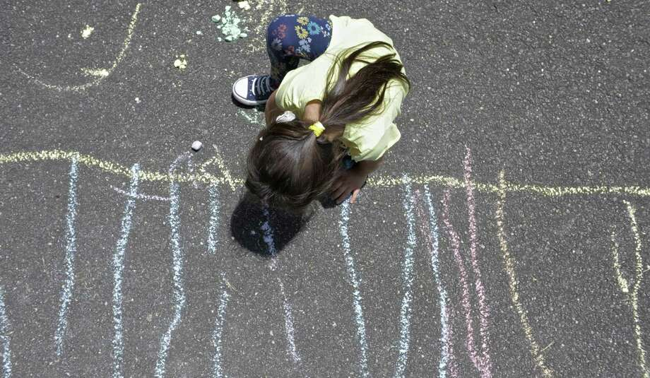 Amy Fajardo colors with chalk during recreation time at the Action Early Learning Center, in Danbury. Thursday, July 6, 2017, in Danbury, Conn. Photo: H John Voorhees III / Hearst Connecticut Media / The News-Times