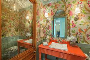 Interior designer Joani Scaff collaborated with Holly Carr in the makeover of the home Holly shares with her husband, Rick. Bright, Asian-inspired colors proliferate in vintage-modern mixed spaces, particularly the first floor, top and middle, for a look that's both fun and elegant. A powder room, above, features brightly colored flowers and birds.