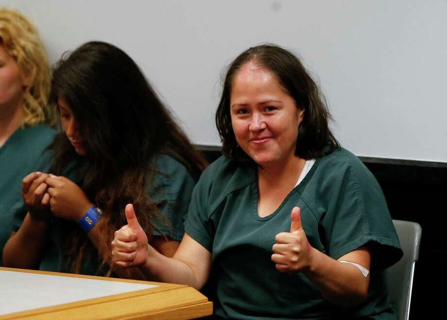 Isabel Martinez gestures towards news cameras during her first court appearance Friday, July 7, 2017, in Lawrenceville , Ga. Martinez is charged with killing four of her children and their father. (AP Photo/John Bazemore) Photo: John Bazemore, STF / Copyright 2017 The Associated Press. All rights reserved.