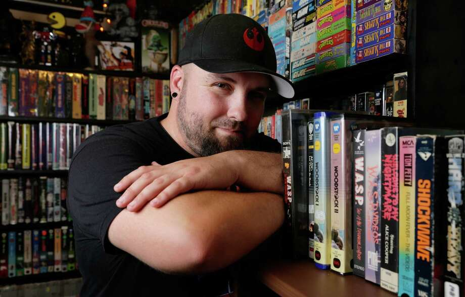 Jason Champion, owner of Champion Video, with the 5000 movie titles on VHS (and some beta) on shelves of his home business, set up in the single car garage at his apartment in Houston, TX, June 20, 2017. (Michael Wyke / For the  Chronicle) Photo: Michael Wyke, Freelance / © 2017 Houston Chronicle