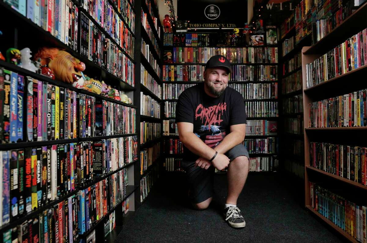 Jason Champion, owner of Champion Video, with the 5000 movie titles on VHS (and some beta) on shelves of his home business, set up in the single car garage at his apartment in Houston, TX, June 20, 2017. (Michael Wyke / For the Chronicle)