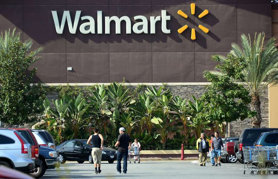 (FILES) This January 29, 2014 file photo shows shoppers outside a Walmart store in Rosemead, California. US retail king Wal-Mart announced October 7, 2104 that it is eliminating health benefits to some 30,000 employees to control rising healthcare costs. The cuts would apply to those employees working fewer than 30 hours per week.  AFP PHOTO / FREDERIC J. BROWN / FILESFREDERIC J. BROWN/AFP/Getty Images Photo: FREDERIC J. BROWN, AFP/Getty Images