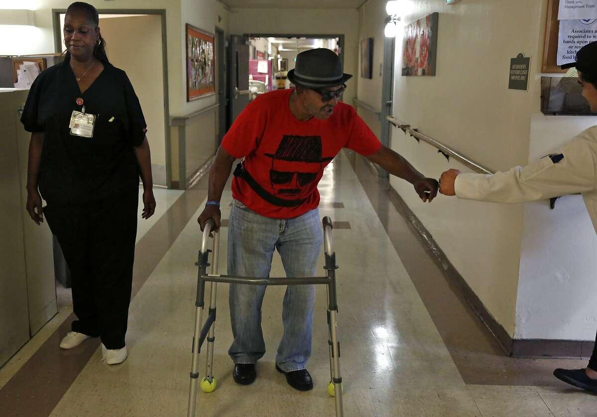 Robert Hawkins, 71, gets a fist bump from lead cook Jonard Espinosa as nurse Hellane Merchant supervises his walk through the hallways the Waters Edge skilled nursing facility in Alameda.