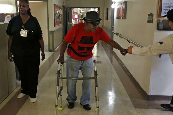 Robert Hawkins, 71, gets a fist bump from lead cook Jonard Espinosa, right, as Hellane Merchant, RNA, supervises his walk through the hallways of the Waters Edge skilled nursing facility July 7, 2017 in Alameda, Calif. Hawkins, who says he was homeless when he was brought to the nursing facility, has been living there for a little over a year. Hawkins says he was very ill when he was brought in and says they saved his life.
